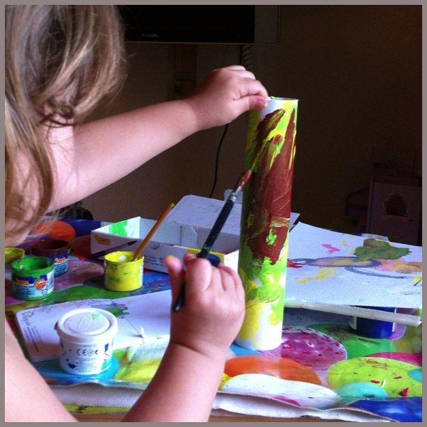 Nena pequeña coloreando un tubo de cartón